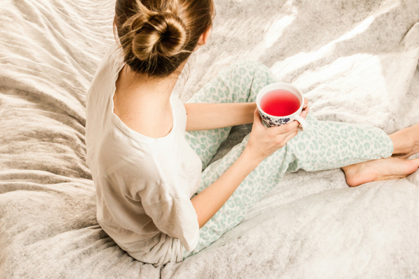 Woman in her PJs drinking tea in bed