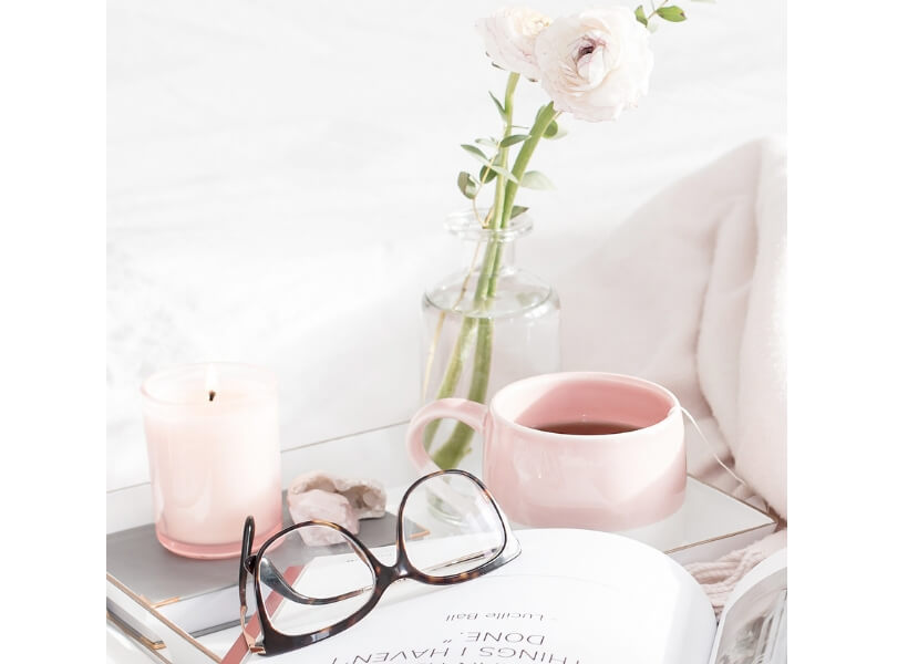 Bed with glasses, lit candle, and a magazine
